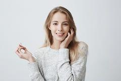 Έννοια μουσικής, ευτυχίας και τεχνολογίας Το καλό όμορφο θηλυκό φορά τη μακριά ξανθή τρίχα της χαλαρά με τα άσπρα ακουστικά Στοκ Φωτογραφία