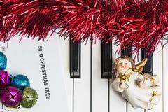 Έννοια μουσικής Χριστουγέννων Τυπωμένη μουσική στο pianto με τα κάλαντα, τον άγγελο και την πούλια Στοκ Εικόνες