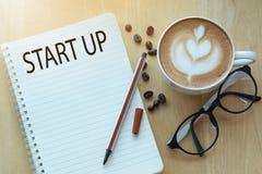 Έννοια ξεκινήματος στο σημειωματάριο με τα γυαλιά, το φλυτζάνι μολυβιών και καφέ Στοκ Εικόνα