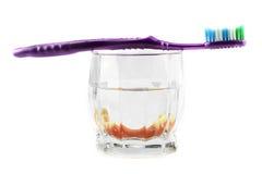 Έννοια οδοντικής υγείας: μερική οδοντοστοιχία μέσα στο γυαλί με την οδοντόβουρτσα στην κορυφή Στοκ Φωτογραφία