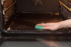 Έννοια οικιακών και οικοκυρικής Τρίψιμο της σόμπας και του φούρνου Κλείστε επάνω του θηλυκού χεριού με το πράσινο σφουγγάρι που κ Στοκ εικόνα με δικαίωμα ελεύθερης χρήσης