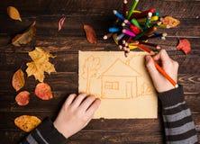Έννοια οικογενειακών σπιτιών Κλείστε επάνω των χεριών ενός παιδιού που σύρει το α Στοκ Φωτογραφία