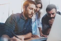 Έννοια ομαδικής εργασίας Νέοι συνάδελφοι που εργάζονται με το νέο επιχειρησιακό πρόγραμμα στο σύγχρονο γραφείο Η ομάδα τριών ανθρ Στοκ φωτογραφία με δικαίωμα ελεύθερης χρήσης