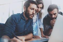 Έννοια ομαδικής εργασίας Νέοι συνάδελφοι που εργάζονται με το νέο επιχειρησιακό πρόγραμμα στο σύγχρονο γραφείο Η ομάδα τριών ανθρ Στοκ Εικόνες