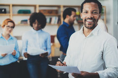 Έννοια ομαδικής εργασίας στο σύγχρονο γραφείο Νέος αφρικανικός επιχειρηματίας που φορά τα άσπρα έγγραφα εκμετάλλευσης πουκάμισων  στοκ εικόνες