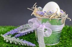 Έννοια Πάσχας - το αυγό σε έναν διακοσμητικό κάδο στη χλόη με το κατάστρωμα σε ένα φωτεινό υπόβαθρο στοκ εικόνα με δικαίωμα ελεύθερης χρήσης