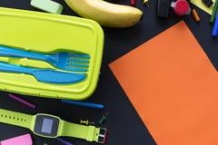 Έννοια πίσω στα χαρτικά καλαθακιών με φαγητό μπανανών σχολικών ρολογιών στο μαύρο υπόβαθρο Στοκ φωτογραφία με δικαίωμα ελεύθερης χρήσης