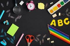 Έννοια, πίσω στο σχολείο Μια φωτογραφία άνωθεν, σε ένα μαύρο υπόβαθρο βρίσκεται πολύχρωμες προμήθειες σχολείων και γραφείων eps α Στοκ εικόνες με δικαίωμα ελεύθερης χρήσης