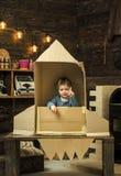 Έννοια παιδικής ηλικίας Το παιδί κάθεται στο χέρι χαρτονιού - γίνοντας πύραυλος, δείχνοντας προς τα πάνω Παιχνίδι αγοριών στο σπί Στοκ Φωτογραφίες