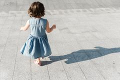 Έννοια παιδικής ηλικίας Το χαριτωμένο προσχολικό κορίτσι τρέχει στοκ εικόνα