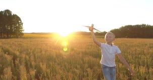 έννοια παιδικής ηλικίας ε Άποψη Copter του χαριτωμένου ξανθού τρεξίματος αγοριών μέσω ενός σπαρμένου τομέα με ένα αεροπλάν φιλμ μικρού μήκους
