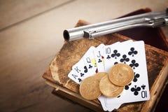 Έννοια παιχνιδιού και εγκλήματος με το πυροβόλο όπλο, τις κάρτες και τα χρυσά νομίσματα Στοκ εικόνες με δικαίωμα ελεύθερης χρήσης