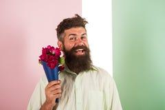 Έννοια παράδοσης λουλουδιών Το άτομο με το εύθυμο πρόσωπο γενειάδων κρατά τα φρέσκα λουλούδια ανθοδεσμών Hipster με τις έτοιμες δ Στοκ Φωτογραφία