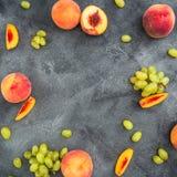 Έννοια πλαισίων φρούτων με τα τεμαχισμένα ροδάκινα και τα πράσινα σταφύλια στο σκοτεινό υπόβαθρο Επίπεδος βάλτε, τοπ άποψη Στοκ Φωτογραφία