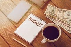 Έννοια πλανίσματος προϋπολογισμών Σημειωματάριο με τον προϋπολογισμό λέξης, κινητό τηλέφωνο, χρήματα, σακούλα Στοκ Εικόνες