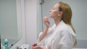 Έννοια προσοχής προσώπου Γυναίκα που εφαρμόζει το καλλυντικό λοσιόν για να φροντίσει το δέρμα στο λουτρό Υγιεινή πρωινού απόθεμα βίντεο