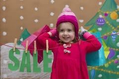 Έννοια πώλησης, Χριστουγέννων, διακοπών και ανθρώπων - χαμογελώντας μωρό στο κόκκινο φόρεμα με το σημάδι και τις τσάντες πώλησης Στοκ Εικόνες
