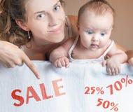 Έννοια πώλησης με το mom και το μωρό που βρίσκεται στο άσπρο κάλυμμα Στοκ Φωτογραφίες