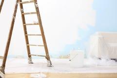 Έννοια σπιτιών ζωγράφων, ξύλινη σκάλα, κάδος, και άσπρος τοίχος Στοκ εικόνα με δικαίωμα ελεύθερης χρήσης