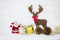 Έννοια στοιχείων Χριστουγέννων, Άγιος Βασίλης με τον ξύλινους τάρανδο και το κιβώτιο δώρων στοκ φωτογραφία