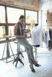 έννοια σχεδιαστών: Σχεδιαστής μόδας που εργάζεται κοντά στο μανεκέν μέσα Στοκ Εικόνες