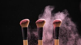 Έννοια σύνθεσης και ομορφιάς Βούρτσα με τη ρόδινη έκρηξη σκονών στο μαύρο υπόβαθρο απόθεμα βίντεο