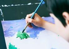 Έννοια τέχνης σχεδίων ζωγραφικής εκμάθησης μικρών παιδιών Το χέρι του παιδιού κρατά μια βούρτσα και τα χρώματα στη Λευκή Βίβλο πρ Στοκ Εικόνα