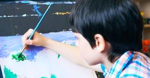 Έννοια τέχνης σχεδίων ζωγραφικής εκμάθησης μικρών παιδιών Το χέρι του παιδιού κρατά μια βούρτσα και τα χρώματα στη Λευκή Βίβλο πρ Στοκ Εικόνες