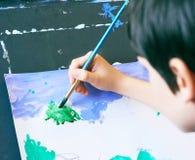 Έννοια τέχνης σχεδίων ζωγραφικής εκμάθησης μικρών παιδιών Το χέρι του παιδιού κρατά μια βούρτσα και τα χρώματα στη Λευκή Βίβλο πρ Στοκ Φωτογραφίες
