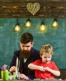 Έννοια ταλέντου και δημιουργικότητας Παιδί και δάσκαλος στα πολυάσχολα πρόσωπα που χρωματίζουν, σχεδιασμός Δάσκαλος με τη γενειάδ Στοκ εικόνες με δικαίωμα ελεύθερης χρήσης