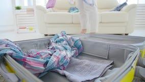 Έννοια ταξιδιού και διακοπών Ενδύματα και ουσία συσκευασίας στη μεγάλη ανοιγμένη βαλίτσα φιλμ μικρού μήκους