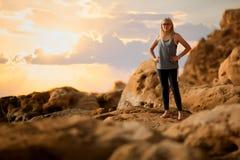 Έννοια ταξιδιού με την πλάτη ενός νέου κοριτσιού ικανότητας που στέκεται σε έναν βράχο και που εξετάζει το τοπίο βουνών Στοκ φωτογραφία με δικαίωμα ελεύθερης χρήσης