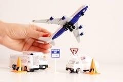 Έννοια ταξιδιού με το παιχνίδι αεροπλάνων εκμετάλλευσης χεριών γυναικών επάνω από την υποδομή αερολιμένων Στοκ Εικόνα