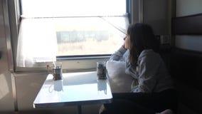Έννοια ταξιδιού σιδηροδρόμων μικρό κορίτσι που φαίνεται έξω το τσάι windowdrinks σε ένα αυτοκίνητο τραίνων διαμερισμάτων ποτά bru φιλμ μικρού μήκους