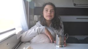 Έννοια ταξιδιού σιδηροδρόμων το μικρό κορίτσι στο παράθυρο πίνει το τσάι τρώγοντας τα μπισκότα σε ένα αυτοκίνητο τραίνων διαμερισ απόθεμα βίντεο
