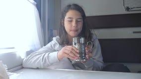 Έννοια ταξιδιού σιδηροδρόμων Το μικρό κορίτσι στο παράθυρο πίνει το τσάι σε ένα αυτοκίνητο τραίνων διαμερισμάτων Το brunette κορι απόθεμα βίντεο