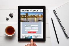 Έννοια ταξιδιωτικού γραφείου στην οθόνη ταμπλετών με τα αντικείμενα γραφείων Στοκ Εικόνες