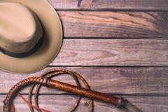 Έννοια ταξιδιού και περιπέτειας Εκλεκτής ποιότητας καπέλο fedora και bullwhip στον ξύλινο πίνακα Τοπ όψη Στοκ Εικόνες