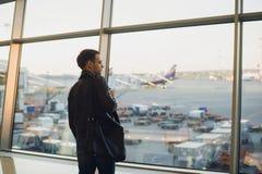 Έννοια ταξιδιού με το νεαρό άνδρα στο εσωτερικό αερολιμένων με την άποψη πόλεων και ένα αεροπλάνο που πετά κοντά Στοκ Εικόνες