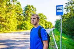 Έννοια ταξιδιού - οδοιπόρος με το σακίδιο πλάτης που στέκεται στη στάση λεωφορείου roa Στοκ Εικόνες
