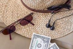 Έννοια ταξιδιού τουρισμού Θηλυκά καπέλο, γυαλιά ηλίου, δολάρια και ακουστικά Στοκ φωτογραφία με δικαίωμα ελεύθερης χρήσης