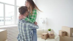 Έννοια της αγοράς και της ενοικίασης της ακίνητης περιουσίας Τυχερό ζεύγος που αγκαλιάζει στο καινούργιο σπίτι απόθεμα βίντεο