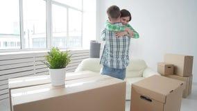 Έννοια της αγοράς και της ενοικίασης της ακίνητης περιουσίας Τυχερό ζεύγος που αγκαλιάζει στο καινούργιο σπίτι φιλμ μικρού μήκους