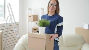Έννοια της ακίνητης περιουσίας και της μόνης ζωής Ευτυχής νέα γυναίκα που κινείται προς το νέο σπίτι φιλμ μικρού μήκους