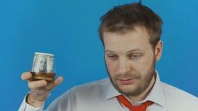 Έννοια της αναταραχής ή του αλκοολισμού χρήσης οινοπνεύματος ως άτομο με τα χρήματα σε ένα ποτήρι του ποτού οινοπνεύματος απόθεμα βίντεο