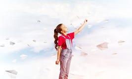 Έννοια της απρόσεκτης ευτυχούς παιδικής ηλικίας με το κορίτσι που ρίχνει το αεροπλάνο εγγράφου Στοκ φωτογραφίες με δικαίωμα ελεύθερης χρήσης