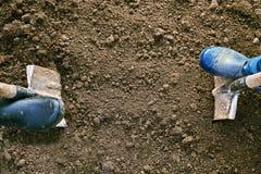 Έννοια της γεωργικής εργασίας Αρσενικά και θηλυκά πόδια στα λαστιχένια παπούτσια που σκάβουν το έδαφος με τα φτυάρια στη γη Στοκ εικόνες με δικαίωμα ελεύθερης χρήσης
