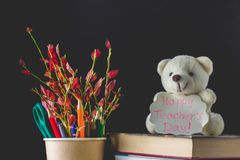 Έννοια της ημέρας του δασκάλου Αντικείμενα σε ένα υπόβαθρο πινάκων κιμωλίας Τα βιβλία, πράσινο μήλο, αντέχουν με ένα σημάδι: Ημέρ Στοκ Φωτογραφία