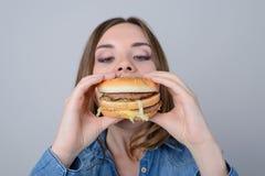 Έννοια της κατανάλωσης των ανθυγειινών πρόχειρων φαγητών Πεινασμένη γυναίκα που δαγκώνει το μεγάλο γούστο στοκ εικόνες