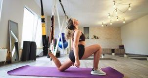Έννοια της νέας γυναίκας τρόπου ζωής υγείας που ασκεί τις αεροβικές ασκήσεις που τεντώνουν τα πόδια που χρησιμοποιούν τις ελαστικ φιλμ μικρού μήκους